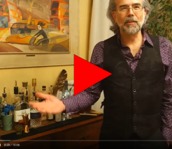 still from a video showing a bartender holding his arms wide